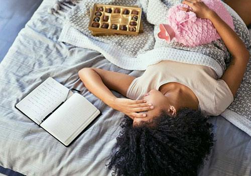 adet krampı çeken kadın yatakta sıcak su torbasıyla yatıyor