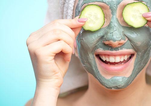 yüzünde maske ve salatalık olan kadın