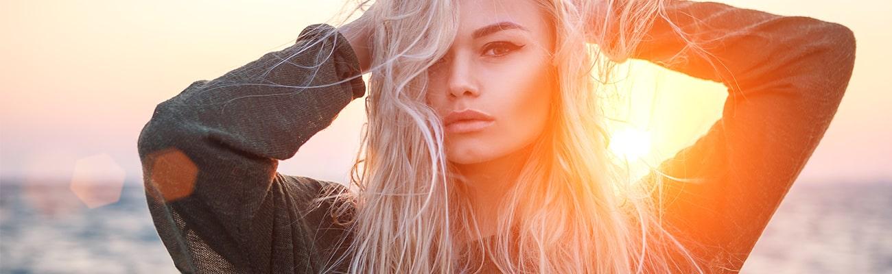 saçlarını tutan arkasında güneş olan kadın